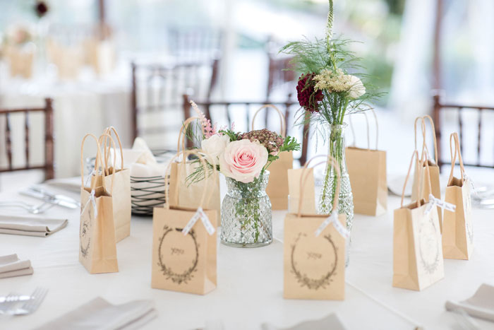 Glass and Floral Centerpieces with Favors on Table